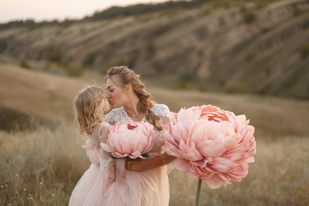 Mom with daughter in pink fairy tale dresses walk in nature