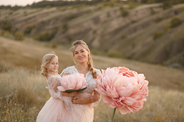 Mom with daughter in pink fairy tale dresses walk in nature ,