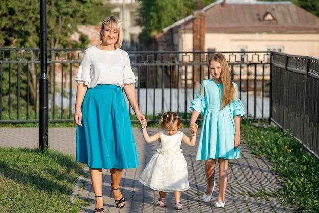 娘を持つお母さんは夏に公園を散歩します。家族の散歩