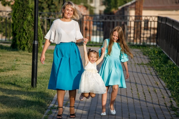 Mom with daughters walks in the park in summer.