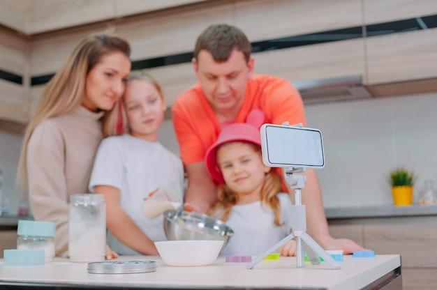 父と一緒のお母さんは、2人の娘に台所で生地を作るように教えています。