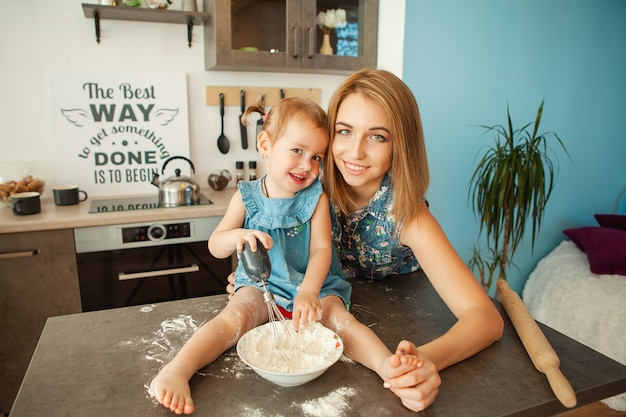 Mom with her 2 years old child cooking holiday pie in the kitchen to mothers day