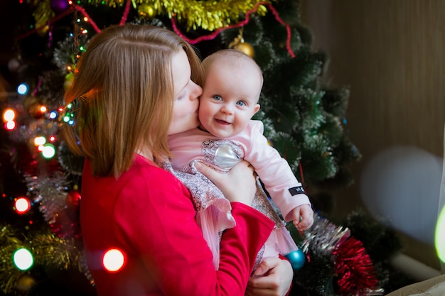 Mom with her baby with a christmas tree
