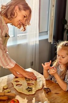 娘と一緒のお母さんは母の日にキッチンで料理をしています。話をして、プロセスを楽しんでください。明るい家のインテリア、明るい部屋でのライフスタイル写真シリーズ