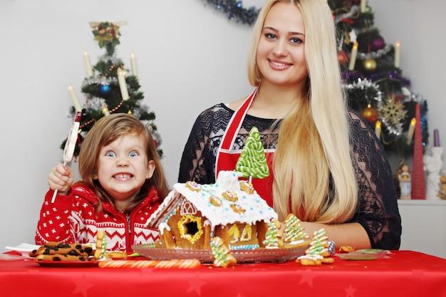 진저 브레드 하우스를 만드는 그녀의 딸과 엄마