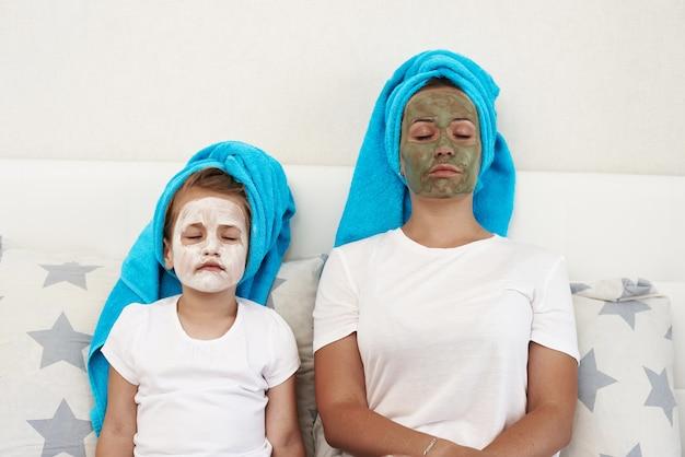 粘土のフェイスマスクを作る彼女の娘を持つお母さん。