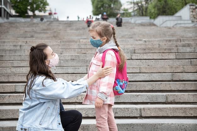 Мама с маленькой дочкой-школьницей на фоне ступенек по дороге в школу. концепция образования пандемии коронавируса.
