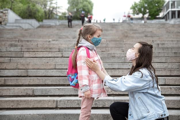 Мама с маленькой дочкой-школьницей на фоне ступенек по дороге в школу.