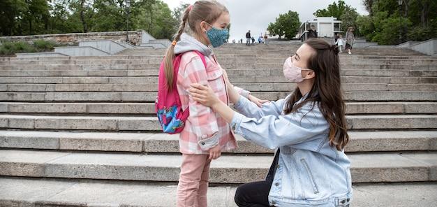Мама с маленькой дочкой, школьницей, по дороге в школу. концепция образования пандемии коронавируса.