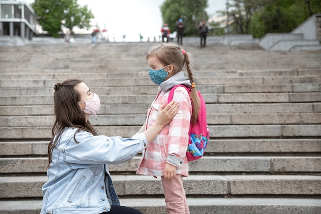 Mom with her little daughter, a schoolgirl, on steps on the way to school. coronavirus pandemic education concept.