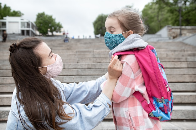 Mom with her little daughter, a schoolgirl, on the way to school. coronavirus pandemic education