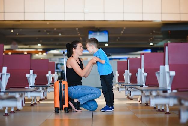 Мама с маленьким сыном и чемоданом в аэропорту