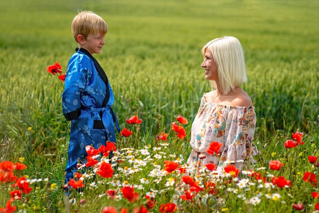 Mom with her son in a magnificent meadow. the boy surprised her mother with red poppies