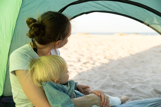 관광 텐트에 앉아 작은 아기와 엄마