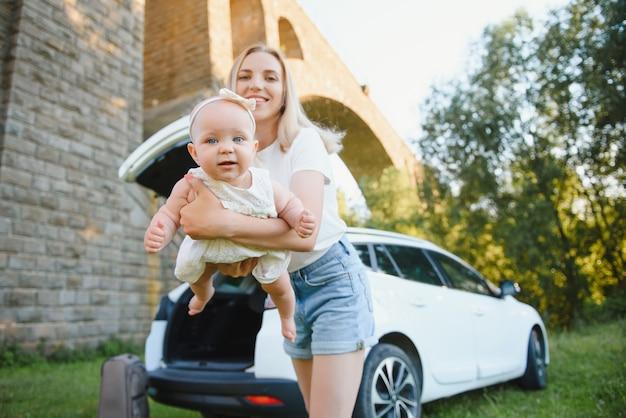 차 근처의 자연 속에서 어린 딸을 둔 엄마