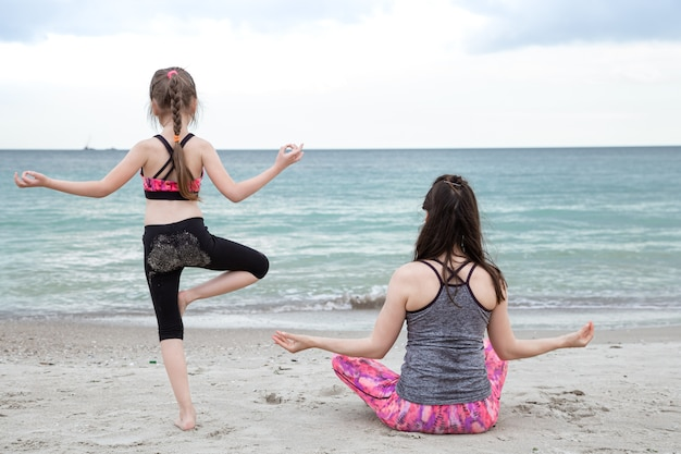 Мама с маленькой дочкой в спортивной одежде занимаются йогой на морском пляже, вид со спины. семейные ценности и здоровый образ жизни.
