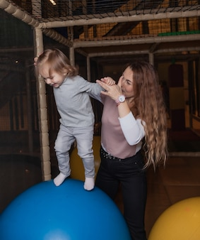 Mom with a little girl play in the children's entertainment center. family holiday