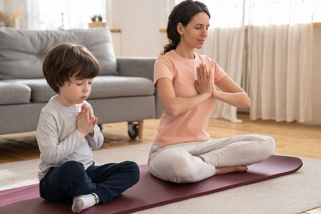 Mom with little son doing yoga exercise, practicing, teaching child to meditate, sit on mat at home.