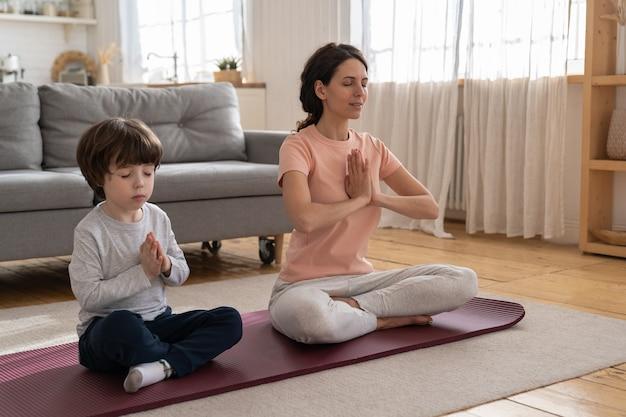 Мама с маленьким сыном делают упражнения йоги, практикуют, учат ребенка медитации, сидят на коврике дома.