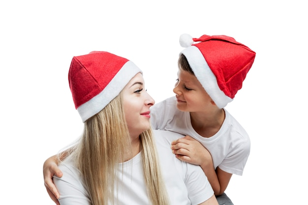 Mom with little son in santa claus hats hug and smile. beautiful people with a festive mood. new year's and christmas. isolated on white .