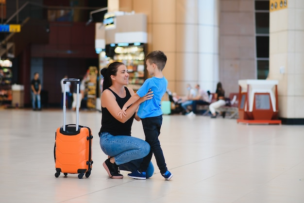 Mom with a little son and a suitcase at the airport. travel concept