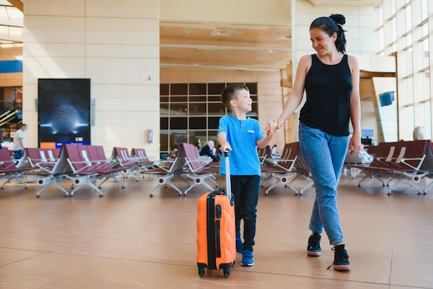Mom with a little son and a suitcase at the airport.