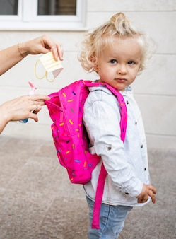 Mom with medical mask putting hand sanitizer in child's backpack