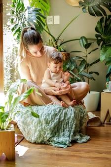 Мама с годовалым ребенком развлекается и сидит в гостиной, украшенной растениями