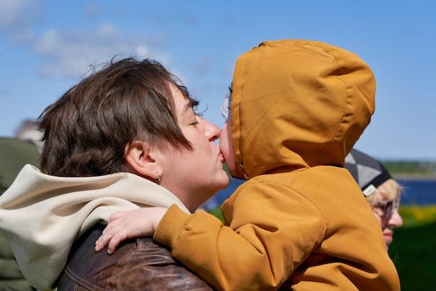Мама с короткими волосами целует своего маленького сына, держа его на руках