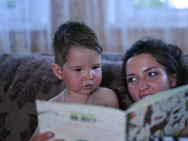 Mom with a small son is reading a book