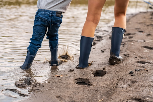 Mom with a small son walks along the sandy shore of the lake in rubber boots. hanging out with children in nature, away from the city