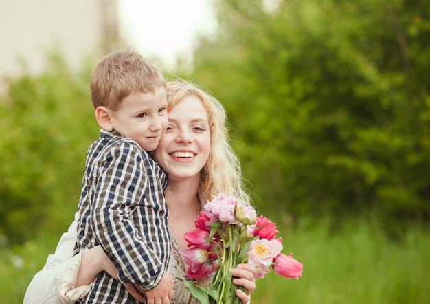 어머니의 날을 위해 아들과 꽃을 가진 엄마