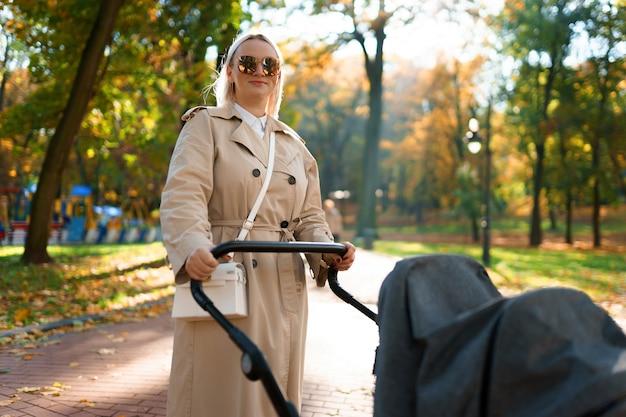 Мама с коляской гуляет в осеннем парке