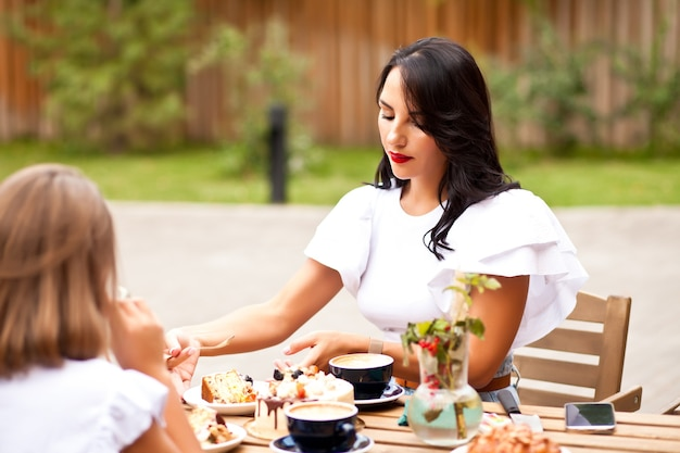 Mom with teen girl sitting in cafe terrace and have a breakfast or branch