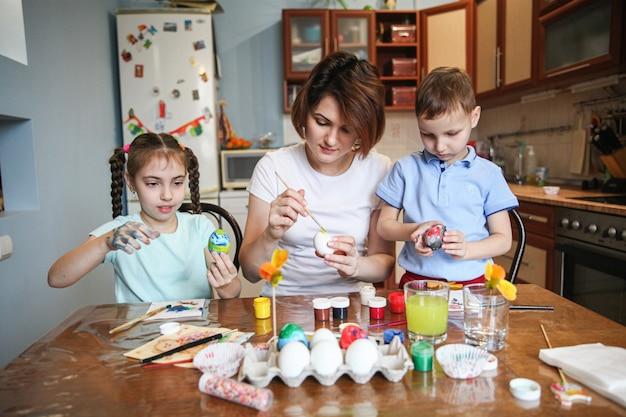 두 아이와 엄마는 부엌에서 집에서 테이블에 앉아 부활절 달걀을 장식