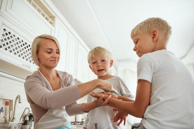 キッチンで休日のパイを調理する2人の息子を持つお母さん。カジュアルリフ