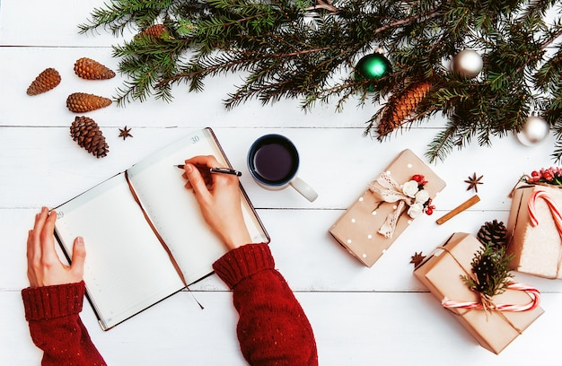 Mom writes to notebook and to-do list of gifts for christmas and new year