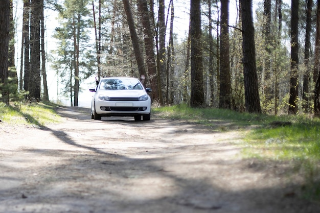 Современный автомобиль едет в лесу. белый автомобиль стоит на лесной проселочной дороге летний солнечный день. водитель и пассажир машут руками