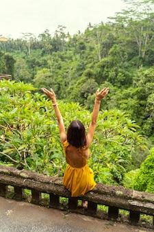 幸せの瞬間。熱帯地方での休暇を楽しみながらジャングルを楽しみにしている若い女性