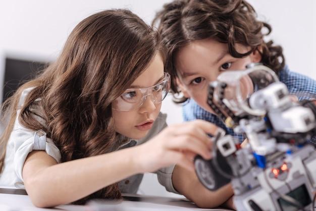 新しい発明の瞬間。スマートな狡猾さは、学校に座って、スキルを示しながらロボットを作成する子供たちを巻き込みました