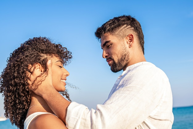 お互いの目を覗き込む幸せな恋人たちの若い多民族カップル間の優しさの瞬間