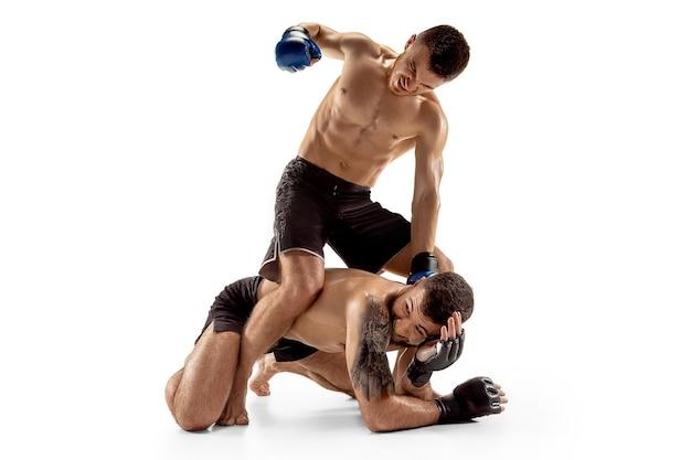 勝利の瞬間。白いスタジオの背景に孤立してポーズをとる2人のプロの戦闘機。健康な筋肉質の白人アスリートまたはボクサーのカップルが戦っています。スポーツ、競争、人間の感情の概念。