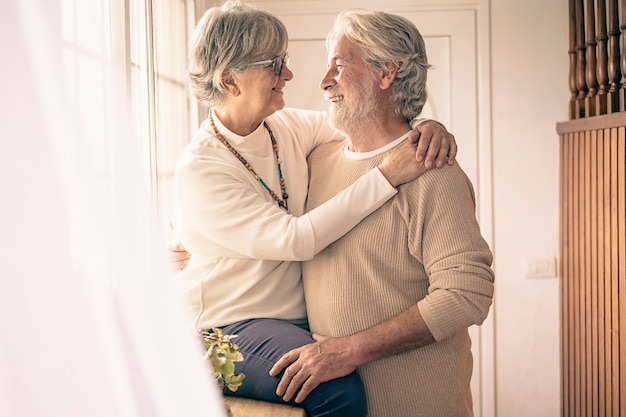 A moment of tenderness between two senior people who hug each other with love in front of the window, looking into each other's eyes. concept of love and happiness