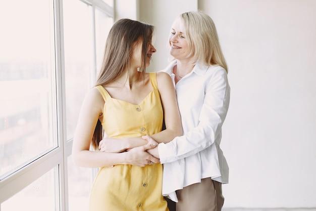 어머니와의 순간. 회색 이상 격리, 미소와 함께 포옹 딸과 함께 매력적인 여자의 사진