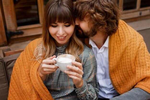 瞬間。テラスに座って、朝のコーヒーを飲みながら朝食を楽しんで愛の低温カップル。