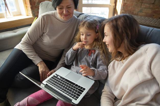 Моменты. счастливая любящая семья. бабушка, мать и дочь проводят время вместе. смотрят кино, используют ноутбук, смеются. день матери, праздник, выходные, праздник и концепция детства.