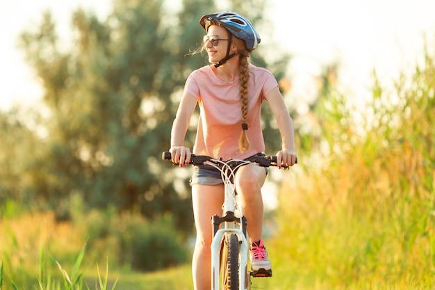 川沿いと牧草地の遊歩道で自転車に乗っている瞬間うれしそうな若い女性