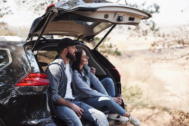 삶의 순간. 자동차 뒷부분에 앉는다. 자연을 즐기고 있습니다. 부부가 새 검은 차를 타고 숲에 도착했습니다.