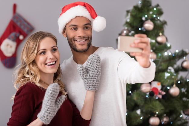 覚えておくべき瞬間。一緒に楽しみながら笑顔で写真を撮る幸せな楽しい若いカップル