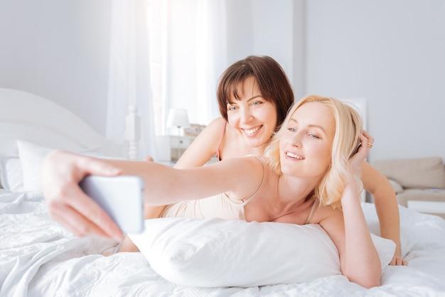 覚えておくべき瞬間。ベッドに横になって、自分撮りをしながら笑っている素敵な陽気な喜んでいる女性